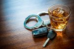Glass of whiskey with car keys and handcuffs - Campbell Law Firm